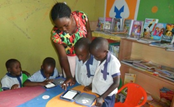 Children being taught how to use e-readers by a book aid international-trained trained librarian