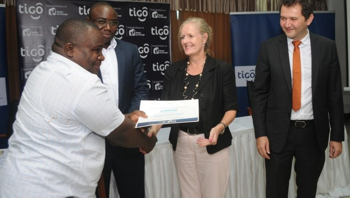 Katarina Rangnitt (2nd right), Swedish Ambassador to Tanzania, awards a certificate to Edward Bihaga, winner of the Tigo Reach For Change competition, in Dar es Salaam as Shavkat Berdiev (right), Tigo Chief Commercial Manager, and Peter Nyanda (left), Resident Chief Executive Officer, Reach For Change, look on