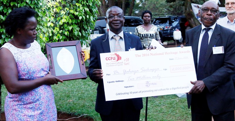 Dr Yahaya Sekagya (centre), the Director of Prometra-Uganda, receives a dummy cheque from Austin Bukenya of Makerere University during the 2nd National Heritage Awards in Kampala.