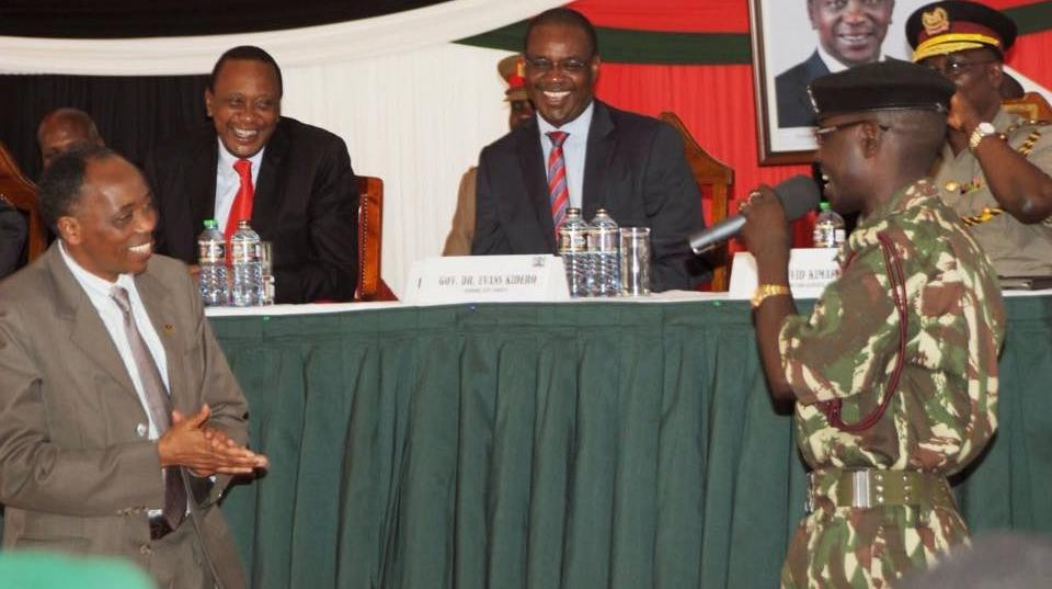 Administration Police officer Sammy Ondimu Ngare entertains dignitaries President Uhuru Kenyatta, Nairobi Governor Evans Kidero, Government Chief of Staff Joseph Kinyua, and former Inspector-General of Police David Kimaiyo.