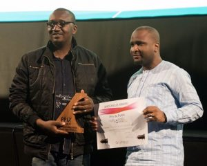 Izu Ojukwu and Moses Babatope hold the joint award to THE WEDDING PARTY and 76 during the closing ceremony of the 5th Nollywoodweek Film Festival.