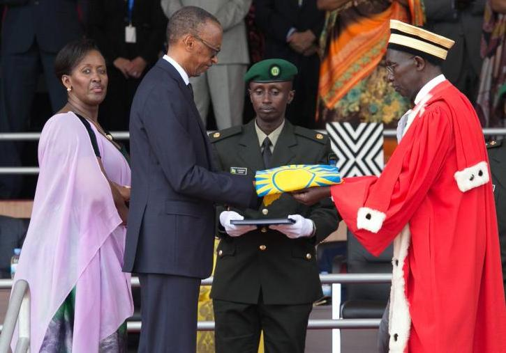 Paul Kagame receives the National flag from Chief Justice Sam Rugege as Jeannette Kagame looks on.