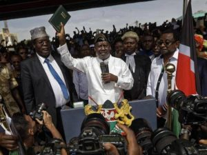 Raila Amolo Odinga, flanked by aides Miguna Miguna and James Orengo, is sworn in as the People's President at Uhuru Park, Nairobi, Kenya.