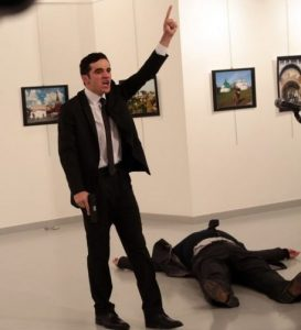 Andrey Karlov, Russia's ambassador to Turkey, lies lifeless on the ground as his killer, Mevlüt Mert Altıntaş, an off-duty Turkish police officer, gun-in-hand, triumphantly raises his index finger to the sky after shooting dead his mark.