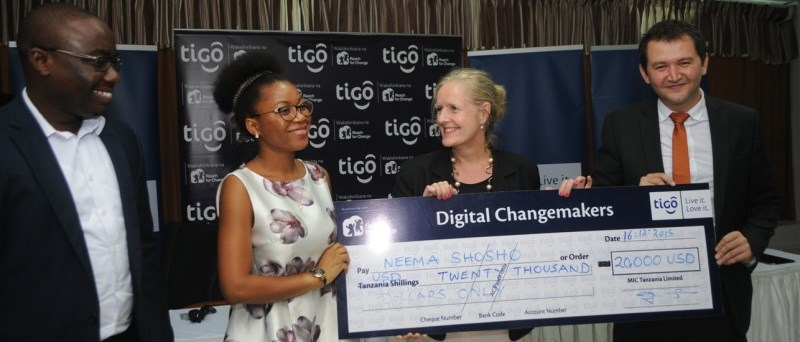 Katarina Rangnitt (2nd right), Swedish Ambassador to Tanzania, awards a model cheque to Neema Shosho, winner of the Tigo Reach For Change competition, in Dar es Salaam as Shavkat Berdiev (right), Tigo Chief Commercial Manager, and Peter Nyanda (left), Resident Chief Executive Officer, Reach For Change, look on