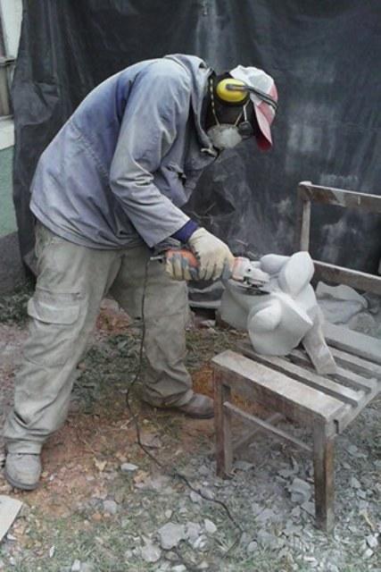 Robin Okeyo Mbera shapes a sculpture in his MberArts premises in Tabaka, Kisii, Kenya