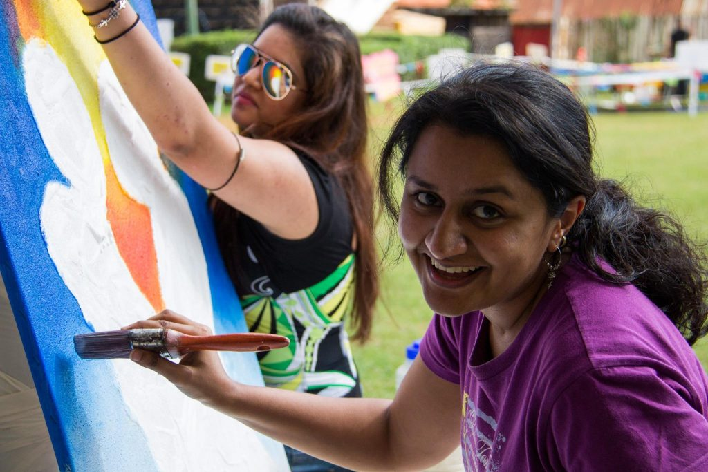 Gemini Vaghela paints during Sondeka festival in Nairobi. With her is Natasha Joshi.