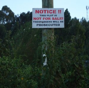 Notice warning the public against encroaching on someone's private land nailed to a Kenya Power 's post