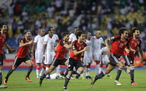 Stunned Burkinabe players stand still as Egyptian players celebrate after beating them in AFCON 2017 semi-final through penalty shootout.(AP Photo/Sunday Alamba)