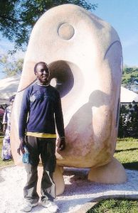 Robin Mbera poses with the bird his magic has freed from a stone in which it had been trapped forcenturies.